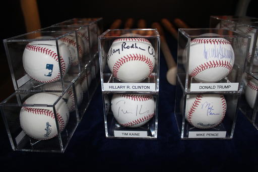 In this photo taken Friday, Sept. 30, 2016, autographed baseballs signed by Democratic and Republican presidential candidates Hillary Clinton and Donald Trump, and their running mates Tim Kaine and Mike Spence, are on display in Garden City, N.Y., at the Cradle of Aviation Museum. Sports fan Randy Kaplan has collected signed baseballs from more than 200 world leaders, including current and former U.S. presidents, prime ministers and others. The exhibit is on display at the museum through next month's election. (AP Photo/Frank Eltman)